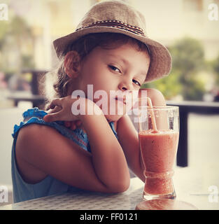 Clever serious kid girl drinking vitamin smoothie juice in street cafe and looking. Toned closeup portrait - Stock Photo