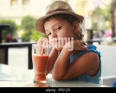Clever serious kid girl drinking vitamin smoothie juice in street cafe and looking - Stock Photo