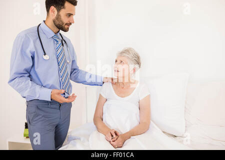 Handsome home nurse talking to elderly woman - Stock Photo