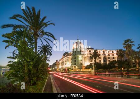 Hotel Negresco on Promenade des Anglais in Nice, palm trees, traffic, twilight, Provence-Alpes-Cote d'Azur, France - Stock Photo