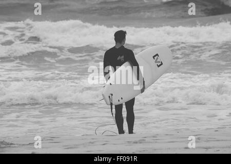 Beach Human Monochrome Ocean Shore Surfboard Surfer Tide Water Wet Suit black and white outdoor person standing - Stock Photo