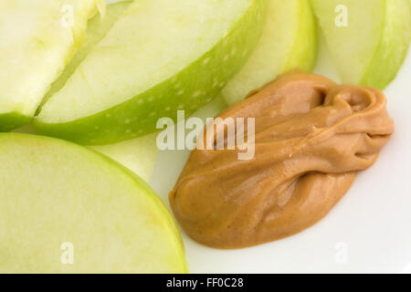 Close view of a group of green apple slices on a dish with a small amount of peanut butter for dipping. - Stock Photo