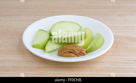 A group of green apple slices on a dish with a small amount of peanut butter for dipping on a wood table top - Stock Photo