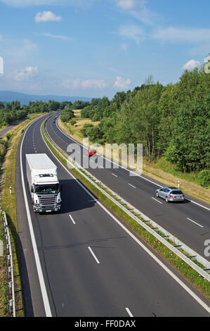 Highway passing through the countryside, going down the highway truck and passenger cars, view from above - Stock Photo