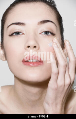 Beautiful young woman applying face lotion - Stock Photo