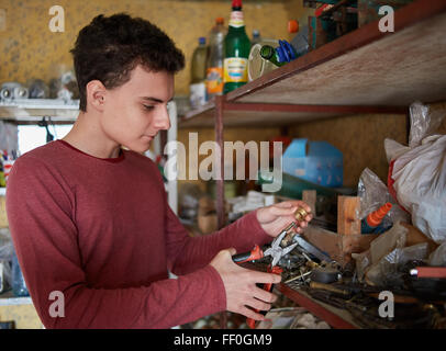 Teenage boy with pliers and various tools doing some diy project - Stock Photo