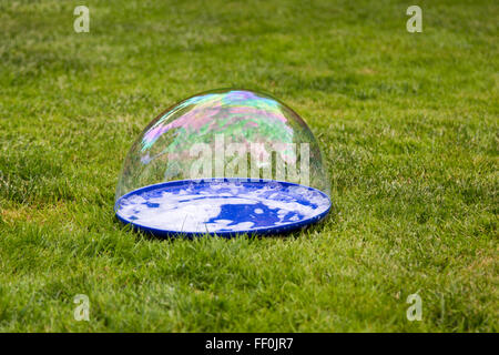 big bubble lies on a plate on the grass - Stock Photo