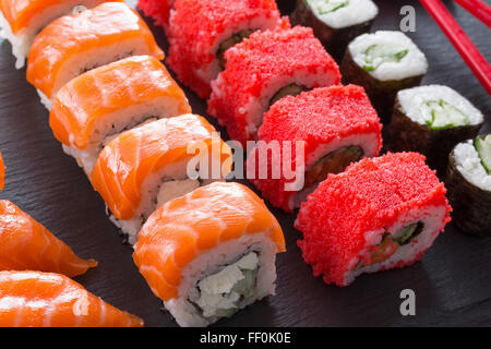 set of sushi and rolls on a slate table. - Stock Photo