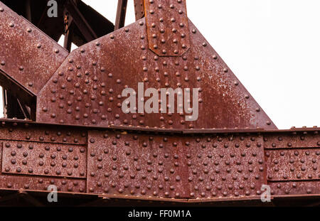 Portion of heavy rusted  red industrial metal joints held together with multiple rivets. - Stock Photo