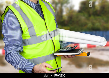 Building surveyor in hi vis carrying site plans and calculator and site plans - Stock Photo