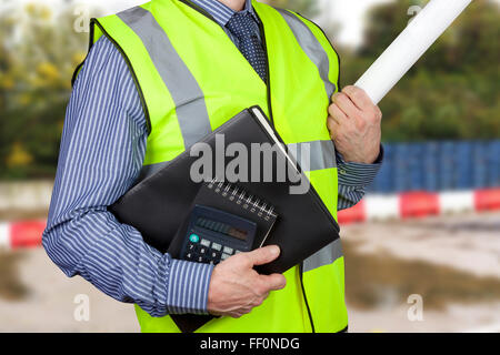 Building surveyor in hi vis carrying work folders and calculator with site plans under his arm - Stock Photo