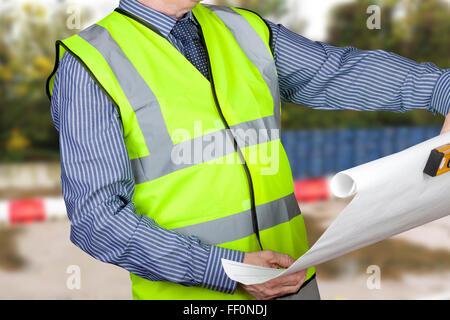 Building surveyor in hi vis checking site plans holding spirit level in a hi viz vest - Stock Photo