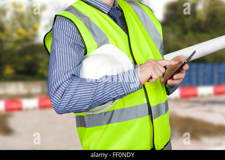 Building surveyor in hi vis vest with site plans checking his smart phone on site - Stock Photo