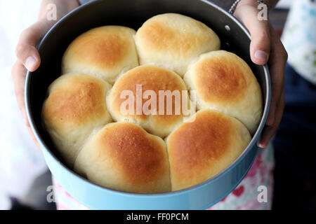 Child hand holding home made baked buns in baking tin - Stock Photo