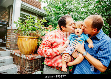 Gay fathers kissing baby son outdoors - Stock Photo