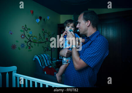 Father giving baby son pacifier in nursery - Stock Photo