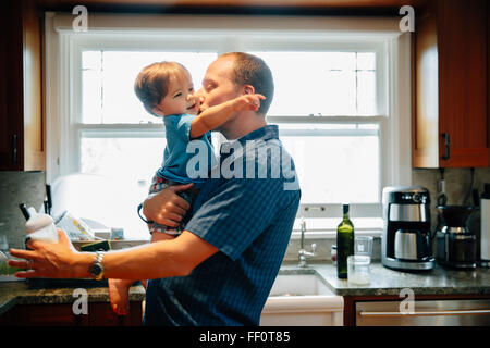 Father kissing baby son in kitchen - Stock Photo