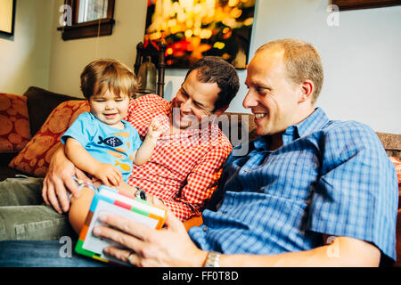 Gay fathers playing with baby son on sofa