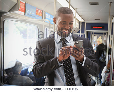 Black businessman using cell phone on subway - Stock Photo