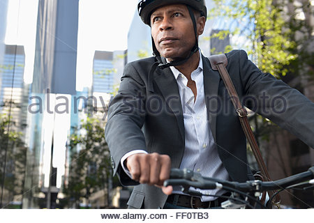 Businessman riding bicycle in city - Stock Photo