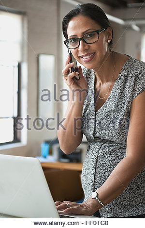 Pregnant businesswoman talking on cell phone in office - Stock Photo