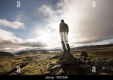 Caucasian man standing on rock in field - Stock Photo