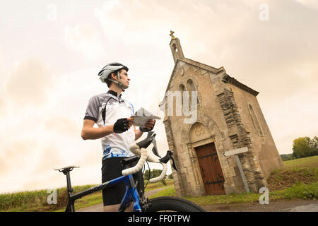 Caucasian cyclist reading map near church - Stock Photo
