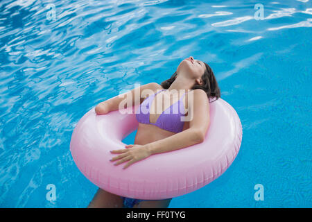 Mixed race amputee woman swimming in pool - Stock Photo