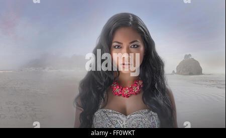 Serious Asian woman on beach - Stock Photo