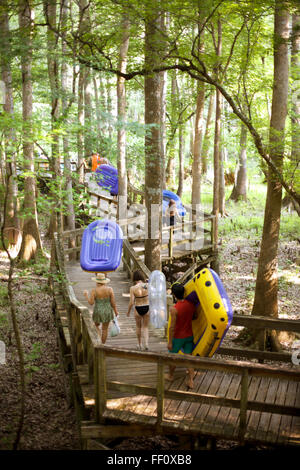 A group of people carry their inflatable rafts along a boardwalk in the Florida woods on their way to float down - Stock Photo