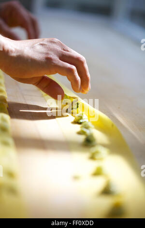 A close-up on hands folding homemade pasta dough over small dots of filling on a wooden counter top. - Stock Photo