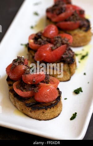 A bite sized appetizer of seasoned meat and cherry tomatoes on top of toast. - Stock Photo
