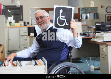 Caucasian businessman holding handicapped sign in office - Stock Photo