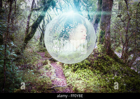 Caucasian man in glowing orb in forest - Stock Photo