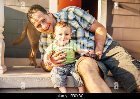 Caucasian father and son sitting on patio - Stock Photo