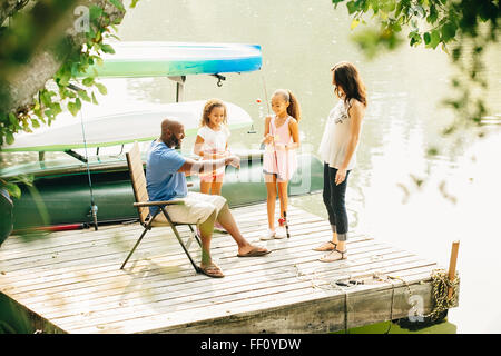 Family standing on dock in lake - Stock Photo