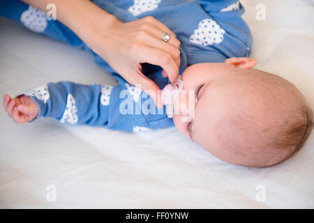 Caucasian mother giving baby daughter pacifier - Stock Photo