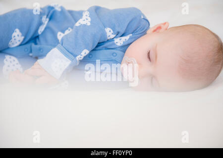 Caucasian baby girl sleeping on bed - Stock Photo