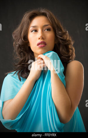 Elegant closeup portrait of beautiful young woman in light blue cape with a faraway look in her eyes, against black - Stock Photo