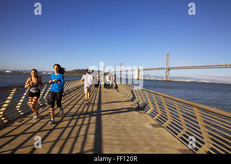 People jogging along San Francisco's Pier 14 on a sunny afternoon with the Bay Bridge in the background. - Stock Photo