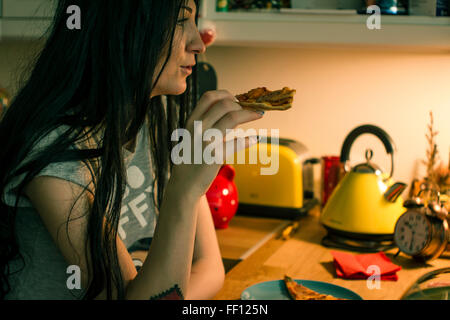 Caucasian woman eating pizza in kitchen - Stock Photo