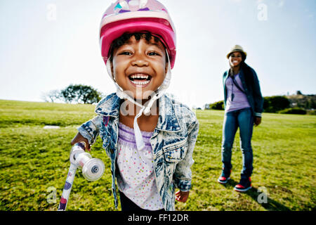 Black mother and daughter playing in park - Stock Photo