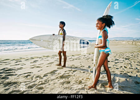 Black mother and daughter carrying surfboards on beach - Stock Photo