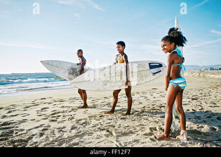 Three generations of Black women carrying surfboards on beach - Stock Photo