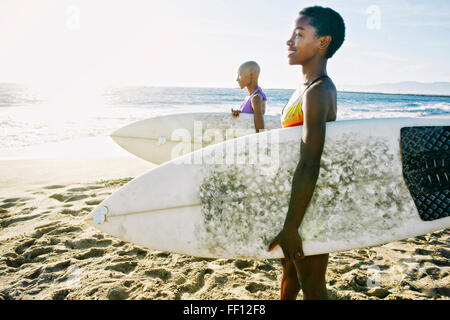 Black women carrying surfboards on beach - Stock Photo