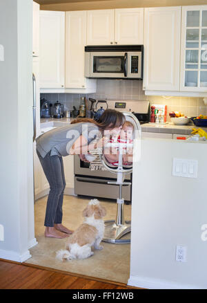 Mixed race mother kissing baby in kitchen
