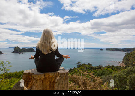 Older Caucasian woman meditating on cliff near ocean - Stock Photo