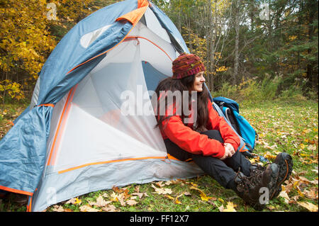 Hiker sitting in tent at campsite - Stock Photo