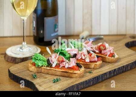 Slices of prosciutto rolled up and arranged on a lettuce leaf. - Stock Photo