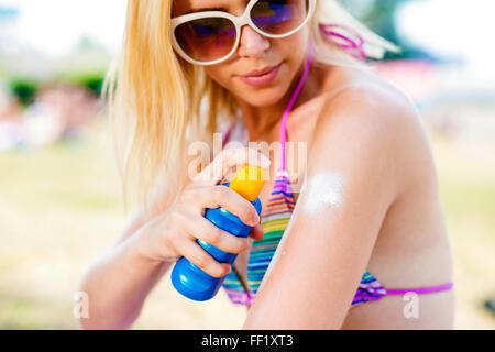 Blond woman in bikini and sunglasses putting on sunscreen - Stock Photo